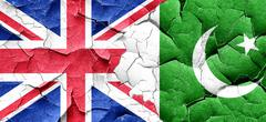 Great britain flag with Pakistan flag on a grunge cracked wall - stock illustration