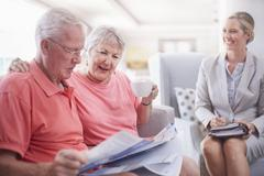Financial advisor discussing paperwork with senior couple Stock Photos