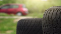 Close up of car tires with traffic in background Stock Footage