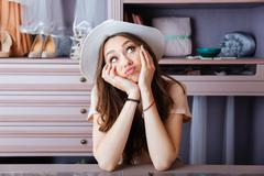 Beautiful young woman thinking about something in her closet - stock photo