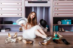 Beautiful young woman sitting in her closet - stock photo