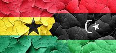 Ghana flag with Libya flag on a grunge cracked wall Piirros