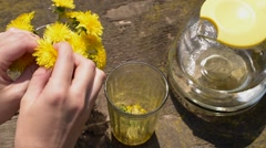 Moving dandelions from bunch to glass Stock Footage
