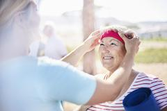 Yoga instructor adjusting senior woman's headband - stock photo