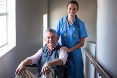 Portrait of smiling senior man and female doctor in corridor Stock Photos