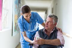 Female doctor giving medicine to senior man in corridor Stock Photos