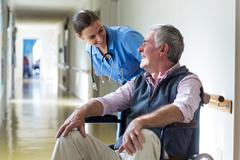 Smiling female doctor and senior man interacting in corridor Stock Photos