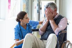 Female doctor consoling senior man in corridor Stock Photos