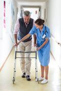 Nurse helping senior patient to walk with walking frame Kuvituskuvat