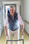 Senior man standing in hospital corridor with walking frame Stock Photos
