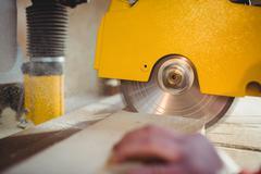 Carpenter sawing a plank of wood Stock Photos