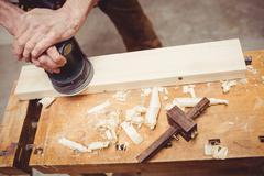 Carpenter sanding down a plank of wood Stock Photos