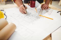 Carpenter drawing on a plan with a compass Stock Photos
