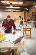 Carpenter using his smartphone while reading plans Stock Photos