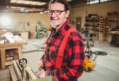 Carpenter sculpting a wood piece Stock Photos