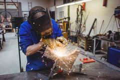 Welder cutting metal with grinder Stock Photos