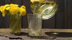 Pouring dandelion tea into a glass - stock footage