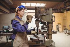 Female welder using a drill press Stock Photos