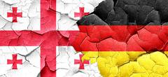 Georgia flag with Germany flag on a grunge cracked wall - stock illustration