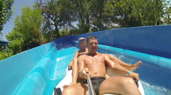 Couple sliding down a water slide at public swimming pool Stock Footage