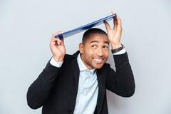 Smiling african american young man hiding under blue clipboard Stock Photos