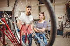 Bicycle repairer colleagues posing behind a bicycle wheel Stock Photos