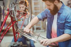 Side portrait of a hipster repairing a bicycle Stock Photos