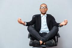Attractive young man in glasses meditating on office chair - stock photo