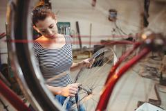 Portrait of woman fixing bicycle behind a bicycle wheel Stock Photos