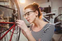 Woman repairing a bicycle wheel Stock Photos