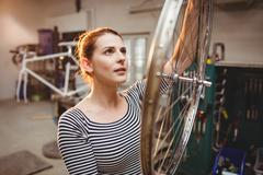 Portrait of woman fixing a bicycle in a bicycle workshop Stock Photos
