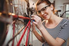 Portrait of woman fixing a bicycle in a bicycle workshop Kuvituskuvat