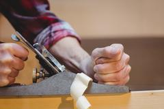 Portrait of carpenter perfecting wood plank form with a work tool Stock Photos