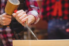 Close-up of carpenter perfecting wood plank form with a mallet Stock Photos