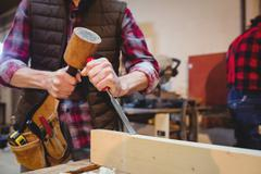 Close-up of carpenter using a mallet on a wood plank Stock Photos