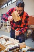 Carpenter working on a wooden plan with an hammer Kuvituskuvat