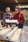 Duo of carpenters studying plans Stock Photos