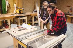 Duo of carpenter working on a wood plank Stock Photos