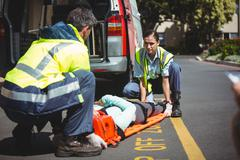 Ambulance crew about to carry a jogger in their vehicle Stock Photos