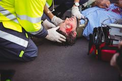 Injured man being taken care of by ambulance crew Stock Photos