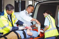 Ambulance crew and doctor taking care of an injured person Stock Photos