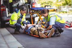 Ambulance crew taking care of an injured person Stock Photos