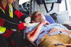 Injured man being taken care of ambulance crew Stock Photos