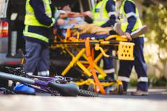 Ambulance crew bringing in the ambulance car an injured man Stock Photos