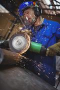 Man cutting metal with circular saw Stock Photos