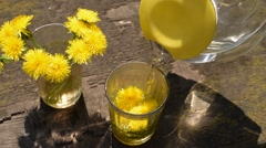 Pouring water into a glass with dandelions - stock footage