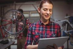 Focus on foreground of woman mechanic using a tablet computer Stock Photos