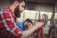 Focus on foreground of mechanic repairing a bicycle Stock Photos