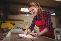 Female carpenter marking on wooden plank with pencil in workshop Stock Photos