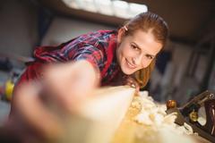 Female carpenter measuring length of wooden plank Stock Photos